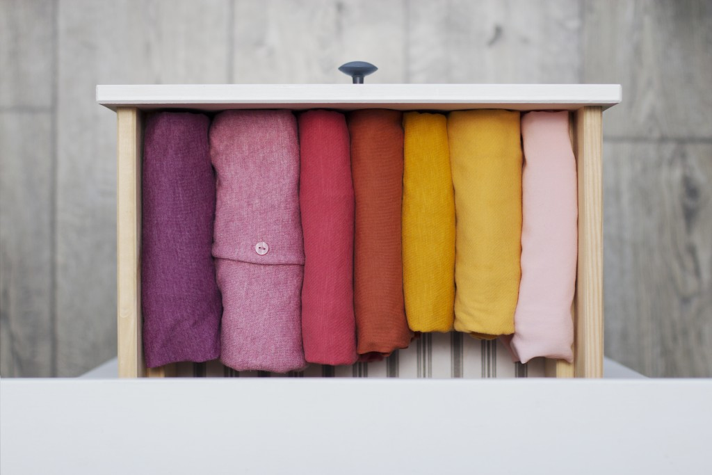 women's clothing yellow, pink and red shades neatly folded in a chest of drawers